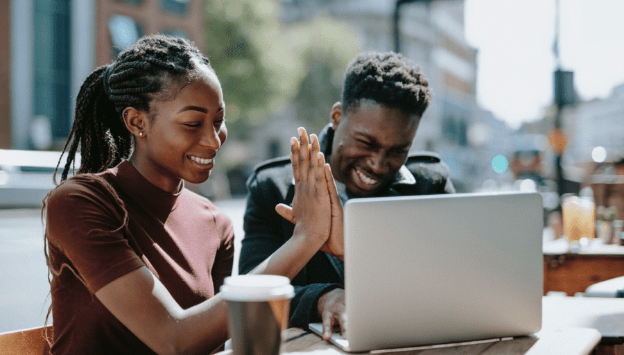 two people high fiving looking at a laptop